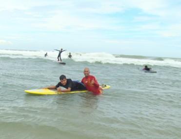 O aluno Vânio Vieira Júnior (na prancha) e o professor Fabinho em uma das aulas de surfe esta semana.
