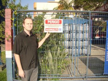 O gerente Matheus Hemkemeier Buss mostra a placa de aviso: é obrigatória a fixação em revendas, mas muitos locais descumprem