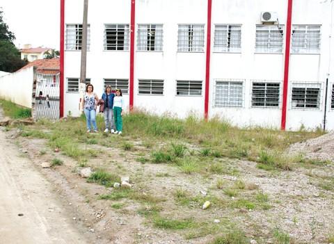Mães e aluna mostram o terreno em que será construída a nova quadra poliesportiva da escola Lino Pessoa