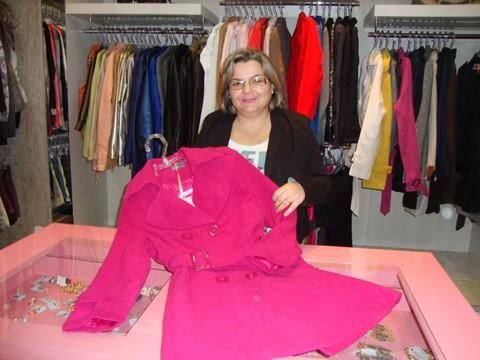 A vendedora Mariléia Ataíde Floriano, da loja Morena Raiz, mostra os casacos que ainda estão nos cabides. Empresário torcem para a chegada do frio para esvaziar os estoques.