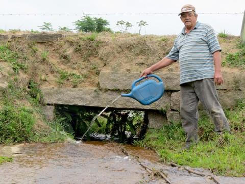 O agricultor Pedro Aroldo Savalaio, de Treze de Maio, durante aplicação do BTI no córrego que passa na propriedade  -  Fotos: Lysiê Santos/Notisul