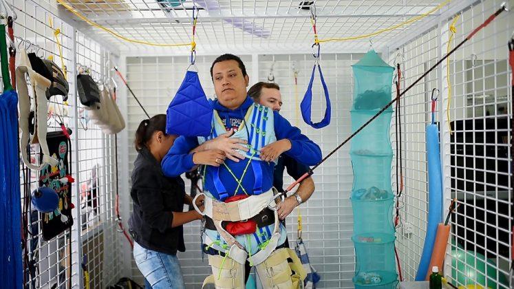 Em pé, Marcelo utiliza uma roupa especial, que tem a função de estabilizar a caixa torácica, que faz com que o diafragma funcione corretamente. Também usam o equipamento em crianças, como mostra a foto ao lado  -  FOTOS: André Fernandes/DRONES SUL/notisul