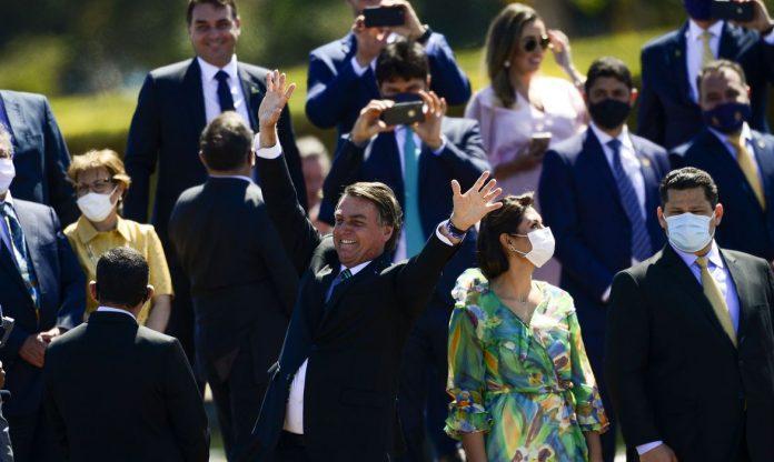 #Pracegover Foto: Na imagem o presidente Jair Bolsonoro acena para populares. Ele estava com outros políticos e autoridades em Brasília. A primeira-dama, Michelle Bolsonaro também estava no local