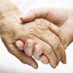 #Pracegover Foto: na imagem uma mão jovem entrelaçada com uma mão de uma pessoa idosa