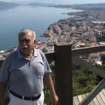 #Pracegover Foto: Na imagem há um homem em um lugar alto, inúmeras casas e o mar