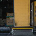 #Pracegover Foto: Há uma imagem de um homem carregando algumas caixas, há caixas no chão e também há um caminhão