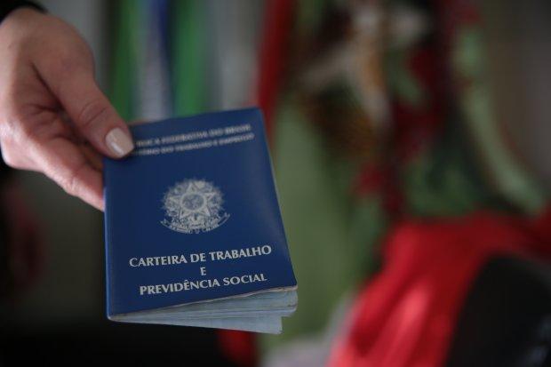 #Pracegover Foto: Na imagem há uma mulher entregando a carteira de trabalho para outra pessoa