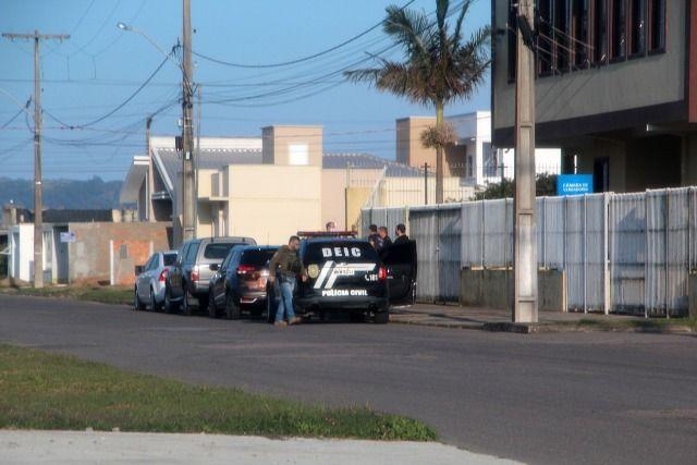 #Pracegover Foto: na imagem há profissionais de segurança pública, viaturas em frente a uma construção, em Laguna