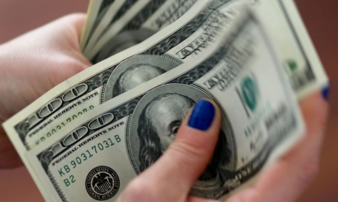 #Pracegover Foto: Na imagem uma mulher segura algumas notas em dólar
