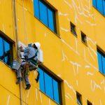 #Pracegover Foto: na imagem há um prédio sendo pintado por um homem