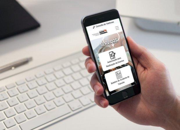 #Pracegover Foto: Na imagem uma pessoa segurando um aparelho de celular e também há um teclado de computador