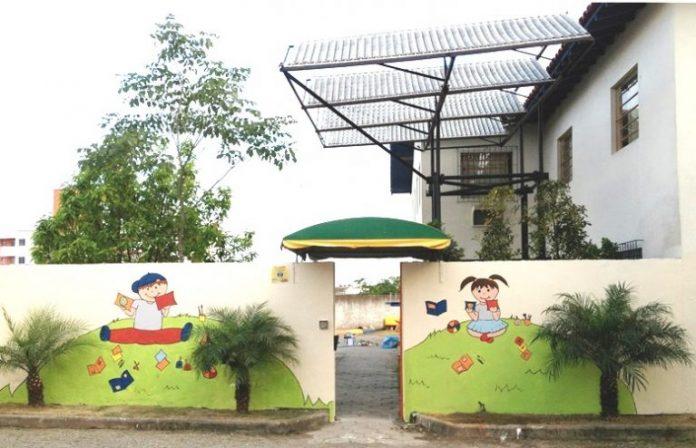 #Pracegover Foto: Na imagem há o prédio da instituição Joanna de Angelis, um muro pintado e com figuras de crianças e em frente ao muro há três plantas