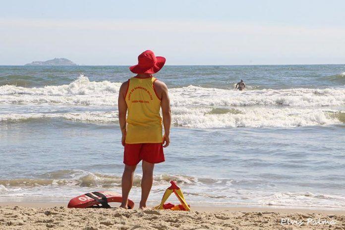 #Pracegover Foto: na imagem há um guarda-vidas na área da praia observando uma pessoa no mar