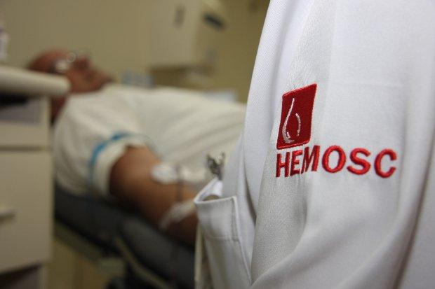#Pracegover Foto: Na imagem há um idoso realizando a doação de sangue e um representante do Hemosc