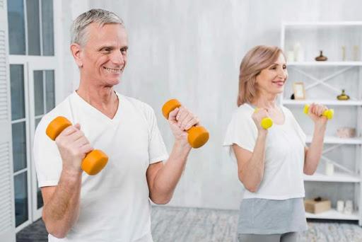 #Pracegover Foto: Na imagem um homem e uma mulher, ambos idosos, realizam exercícios físicos em um cômodo amplo em casa
