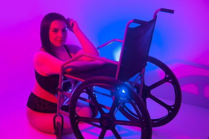 #Pracegover Foto: na imagem há uma linda mulher cadeirante no chão de lingerie, com um braço na cadeira de rodas, com o cotovelo esquerdo na cadeira e a mão esquerda na cabeça