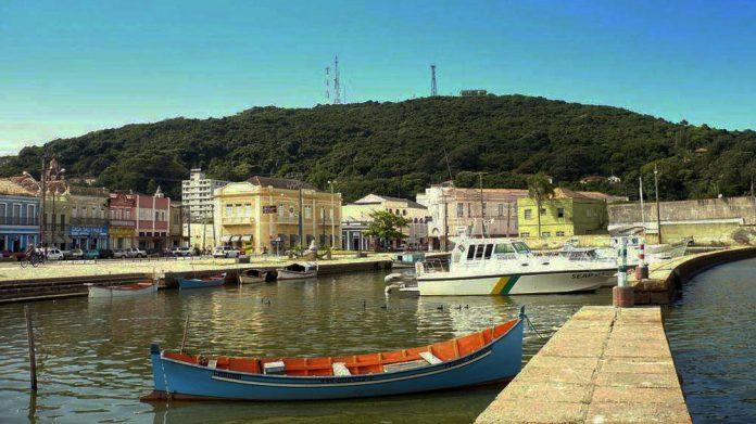 #Pracegover Foto: Na imagem há algumas casas ao fundo, botes e uma lagoa