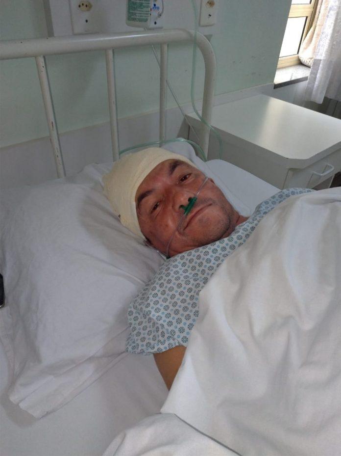 #Pracegover Foto: Um homem deitado em uma cama de hospital. Ele está com uma faixa na cabeça e com sonda no nariz