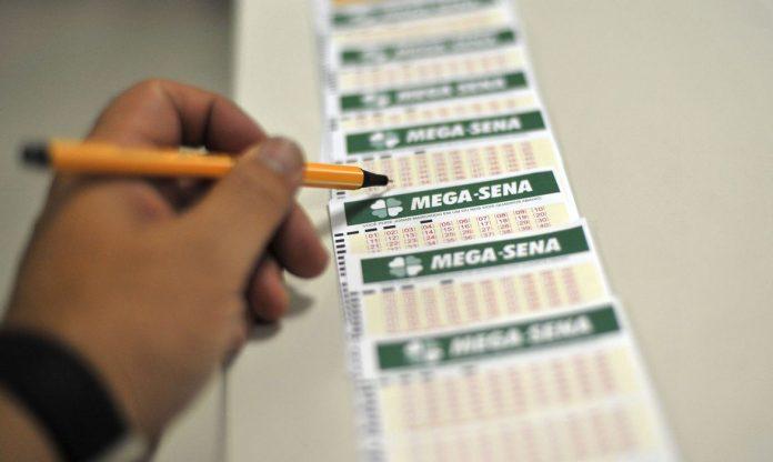#Pracegover Foto: na imagem há cartões da Mega-Sena e uma mão de uma pessoa com uma caneta anotando os números