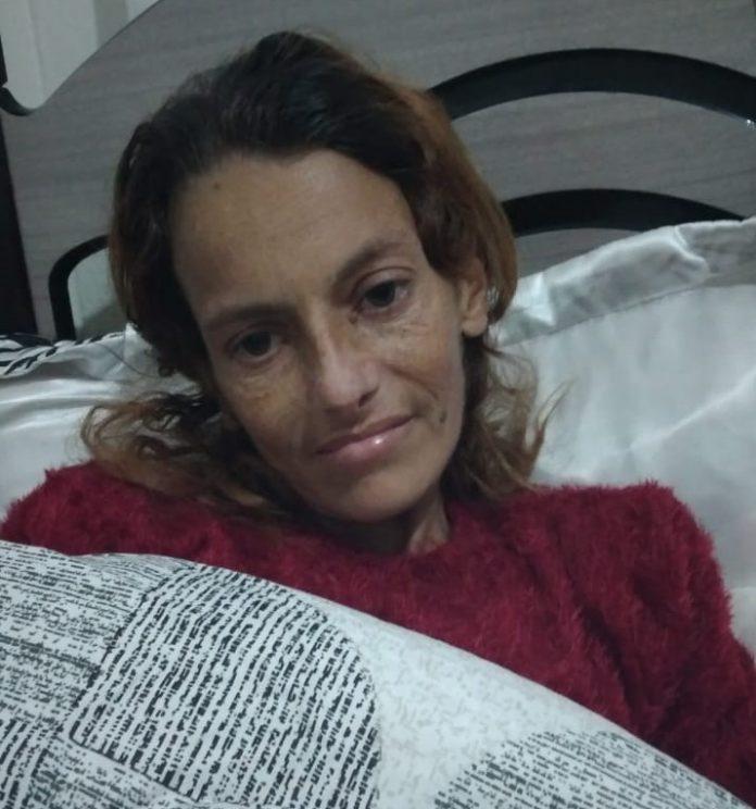 #Pracegover Foto: Na imagem há uma mulher em uma cama, com roupas de inverno e com cobertor