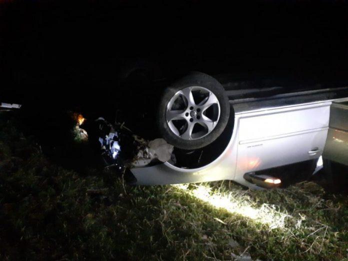 #Pracegover Foto: na imagem há um veículo de cor cinza, que capotou em um gramado na noite deste sábado