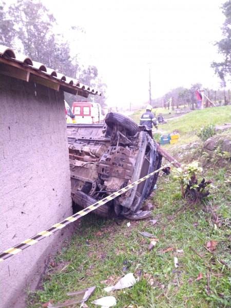 #Pracegover Foto: Na imagem há um carro capotado em cima de um gramado, uma casa salpicada, um profissional do Corpo de Bombeiros e o carro da corporação