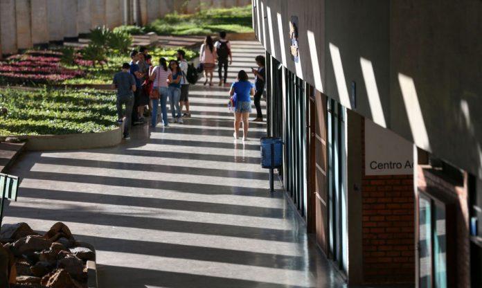 Pracegover Foto: na imagem há vários estudantes em um pátio de uma universidade conversando
