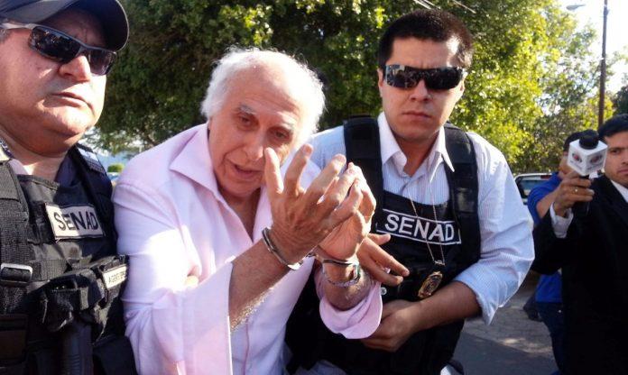 #Pracegover Foto: Na imagem o médico Roger Abdelmassih está algemado ao lado de dois policiais