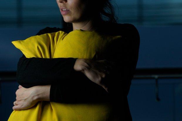 #Pracegover Foto: Na imagem há uma mulher de roupa preta, abraçada com uma almofada amarela e de semblante triste