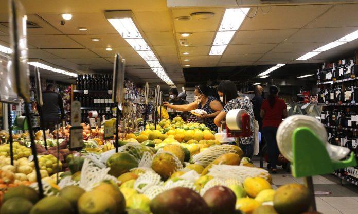 #Pracegover Foto: Na imagem há pessoas escolhendo alimentos como frutas e verduras em um supermercado