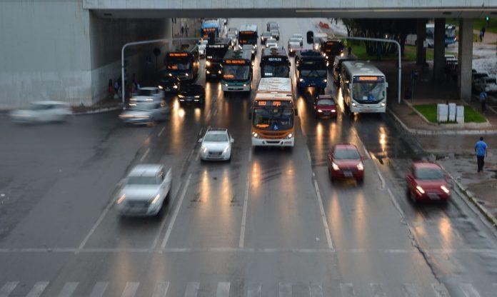 #Pracegover: Há uma rodovia com trânsito intenso de carros, ônibus e com pessoas próximas ao local