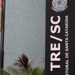 #Pracegover Foto: na imagem aparece o prédio do Tribunal Regional Eleitoral (TRE/SC). Na frente do local há uma placa com a sigla do tribunal