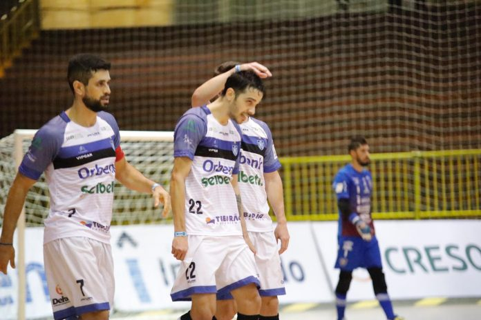 #Pracegover Foto: Na imagem há três atletas do Tubarão Futsal e ao fundo um jogador do Campo Mourão em uma quadra de esportes