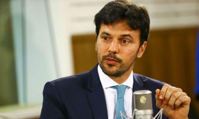#Pracegover Foto: Na imagem o ministro das Comunicações, Fábio Faria, está de terno, sentado e participando de uma entrevista
