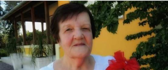 #Pracegover Foto: na imagem há uma senhora e nos fundos uma casa de cor amarela