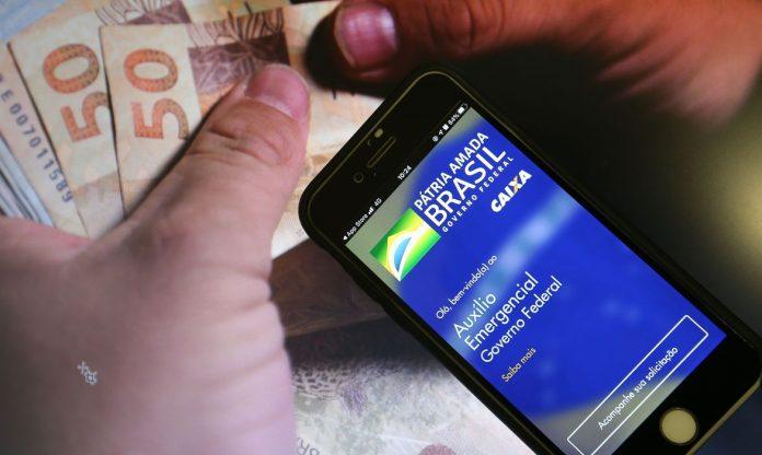 #Pracegover Foto: na imagem há cédulas de R$ 50 e 100. Uma pessoa segurando um celular