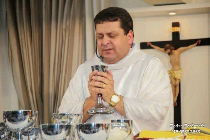 #Pracegover Foto: na imagem há um padre, em suas mãos um cibório e sobre o altar alguns cibórios e na parede um crucifixo