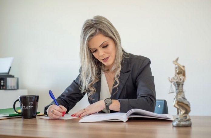 #Pracegover Foto: há uma mulher escrevendo e sobre a mesa uma caneca, um livro e uma imagem