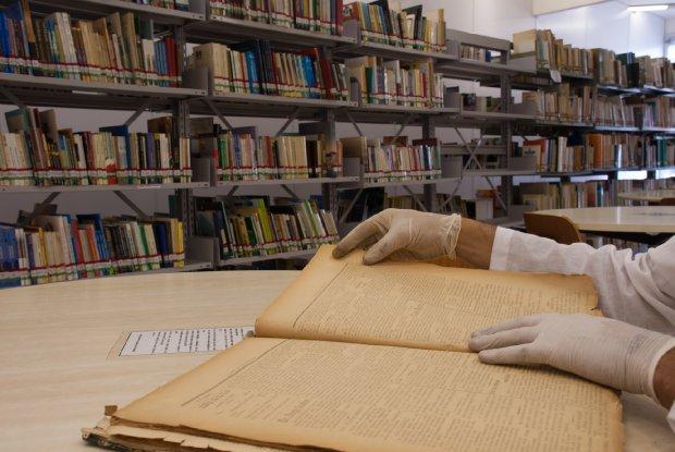 #Pracegover Foto: na imagem uma pessoa realiza pesquisa em um livro. No local há uma biblioteca