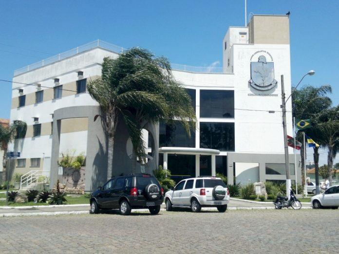 #Pracegover Foto: na imagem há um prédio, três carros, árvores e uma rua calçada