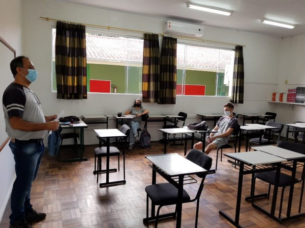 #Pracegover Foto: na imagem há uma sala de aula com várias carteiras, cortinas, janelas, um professor e dois alunos