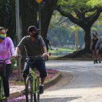#Pracegover Foto: na imagem há uma rua asfaltada, árvores, pessoas caminhando e duas pessoas andando de bicicleta