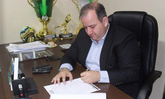 #Pracegover Foto: na imagem há um homem de terno preto e camisa azul. Ele está sentado e assinando papéis. Sobre a mesa há troféus, celuares, um aparelho de telefone fixo, carimbo e folhas