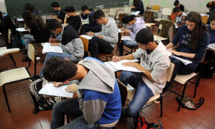 #Pracegover Foto: na imagem há a dezenas de estudantes, folhas e carteiras