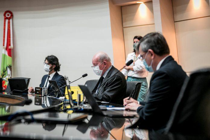 #Pracegover Foto: na imagem há quatro pessoas, microfones, notebooks, uma mesa e cadeiras