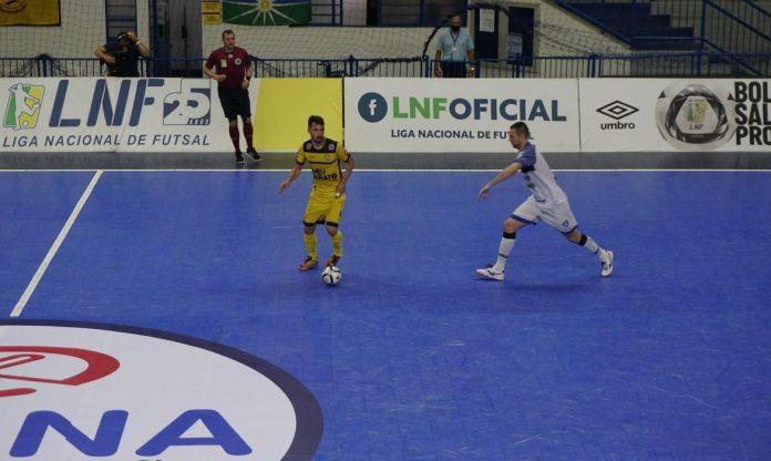 #Pracegover Foto: na imagem há dois jogadores de times opostos, um árbitro e uma bola