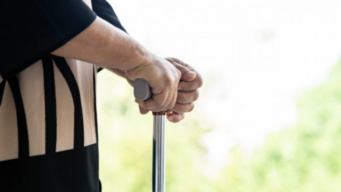 #Pracegover Foto: na imagem uma idosa segurando uma bengala