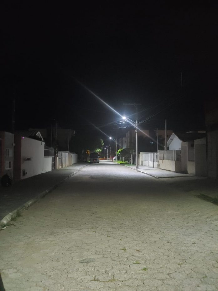 #Pracegover Foto: na imagem há um rua calçada, muros e postes com baixa iluminação