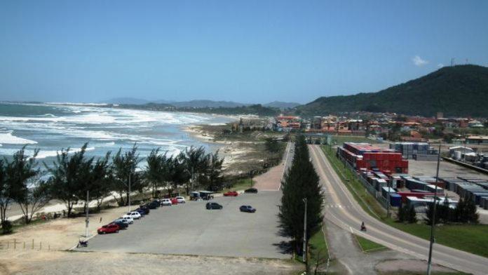#Pracegover Foto: no local há ruas calçadas, árvores, carros e uma praia em Imbituba
