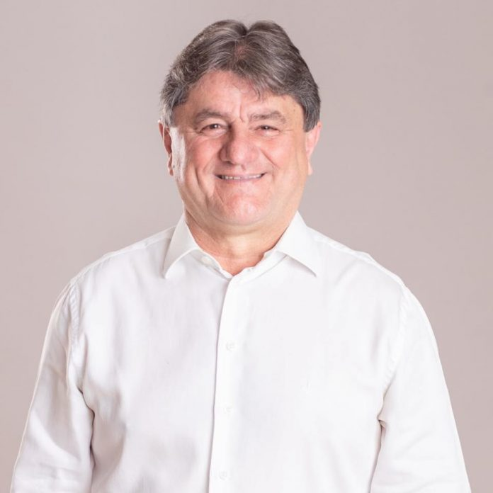 #Pracegover Foto: na imagem há um homem sorrindo. Ele veste uma camisa branca